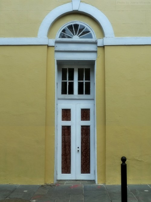 Yellow wall with white arched doorway in Nola