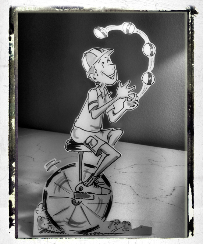 "Black and white photo of little cartoon juggler ""paper doll"" on unicycle, by Joana Miranda"
