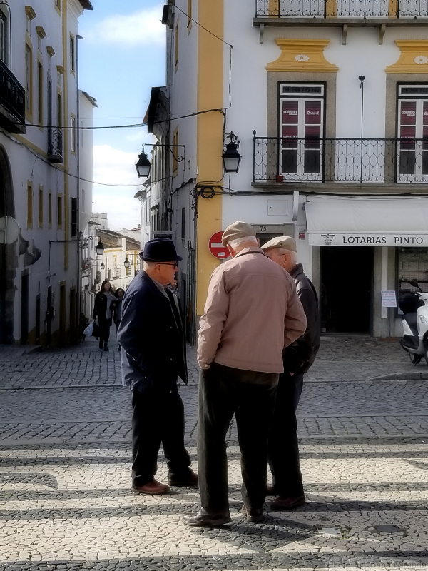 Three friends catch up with the local gossip in the Evora town square