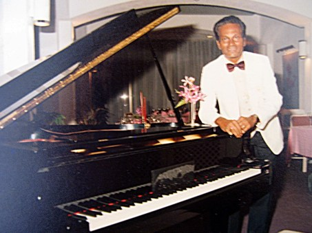 Peter Pragas Malaysian pianist composer standing at a grand piano wearing white tuxedo