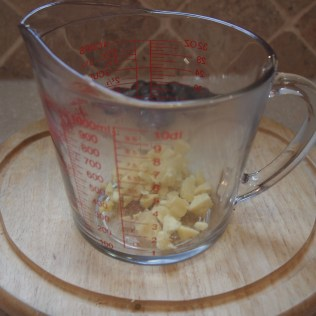 Put the ginger at the bottom of a heat resistant glass measure cup or teapot