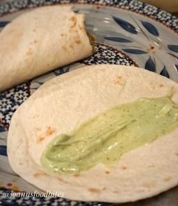 Flat flour tortilla with avocado ranch sauce in a single line streak on the tortilla