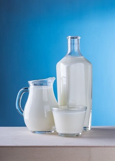 pitchers of milk with a blue background