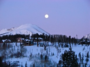 Photograph of the moon setting over Buffalo Mountain, with the alpenglow preceding the sunrise