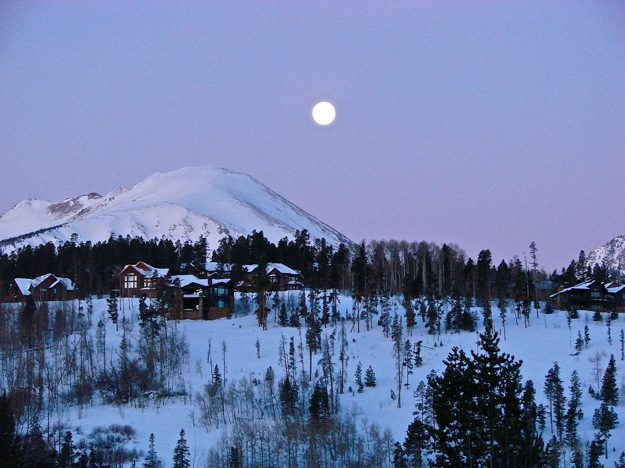 Photograph of the moon setting over Buffalo Mountain, in Silverthorne, CO, with the alpenglow preceding the sunrise
