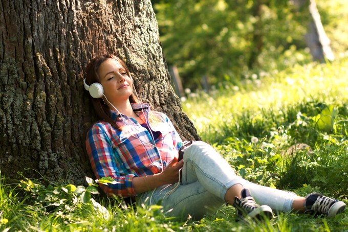 Young woman sitting in the park and listening the music from a smart phone