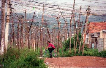"""ORG XMIT: 373601_1.tif Poste com centenas de ligaÁıes elÈtricas clandestinas conhecidas como """"gatos"""" no Jardim Pantanal, bairro da zona leste de S""""o Paulo. (S""""o Paulo (SP), 24.01.2001. Foto de Jo""""o Wainer/Folhapress. Negativo: SP 01082-2001)"""