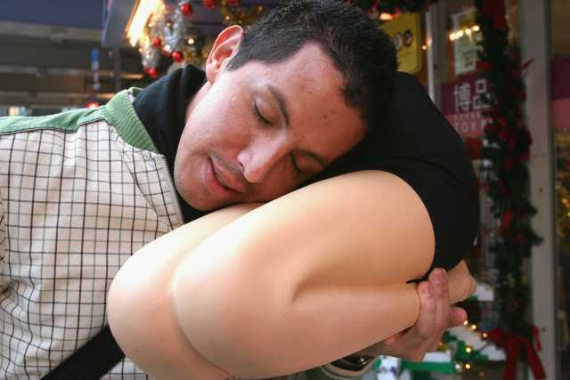 "TOKYO, JAPAN - DECEMBER 14: A tourist tries out a ""Hizamakura"", or lap pillow at Hakuhinkan toy shop on December 14, 2004 in Tokyo, Japan. The ""Hizamakura"", priced at 8,980 yen (86 USD), is a life-size pillow in the shape of a woman's hip and legs and is one of popular prize items for the Christmas and year-end parties. (Photo by Koichi Kamoshida/Getty Images)"