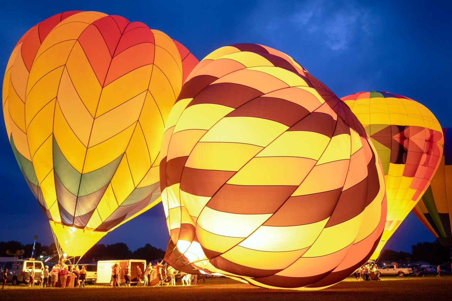 group of people preparing bright air balloons to fly