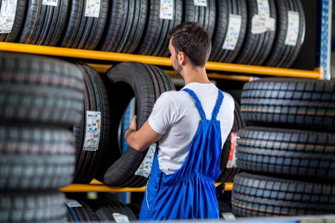 Mécanicien selectionnant un pneu neuf en rayon dans un atelier