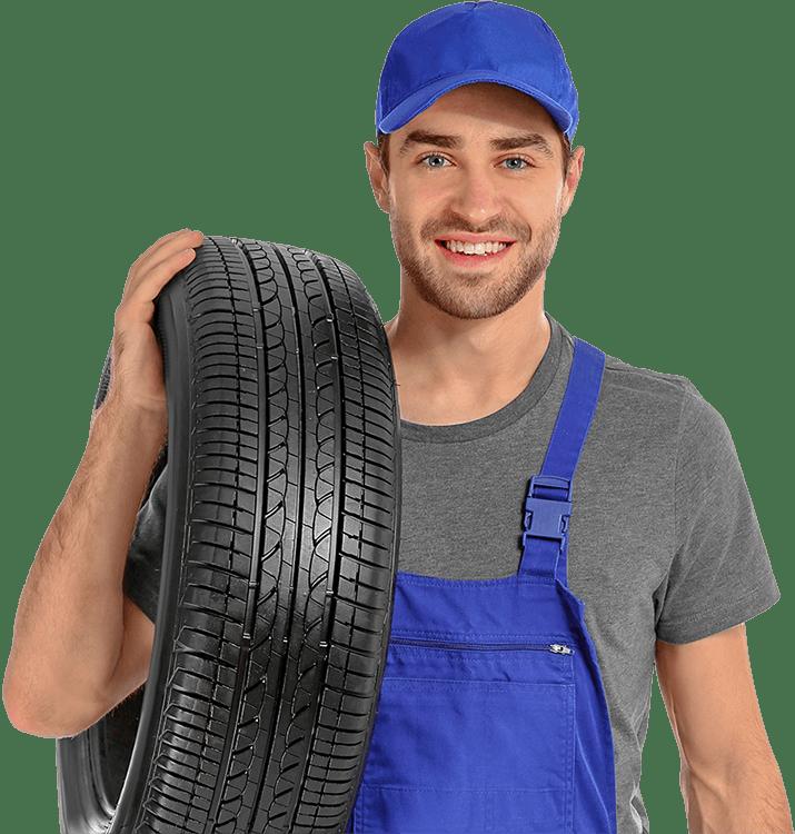 Photographie d'un penumaticien souriant en bleu de travail avec un pneu neuf à l'épaule.
