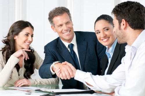 Steps to Hiring a New Employee - team smiling-with handshake