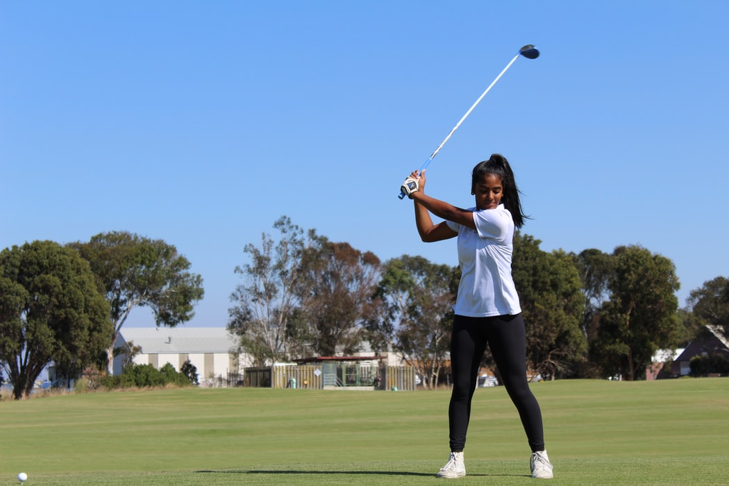 A lady practices her golf swing. Maybe she's already aware of all the reasons why golf is good for business.