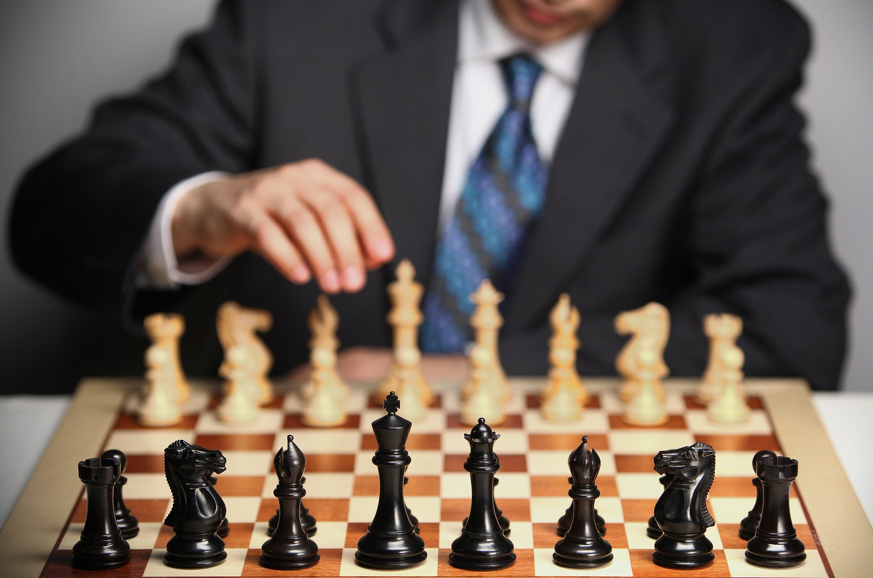 A man plays chess, the classic strategy game. Candidate attraction relies on a robust strategy.