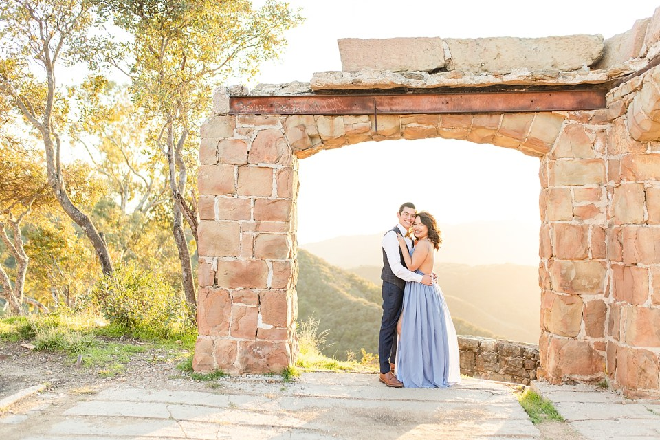 The happy couple is smiling at the camera while holding each other close and standing under the arch during their magical Knapp's Castle engagement session.
