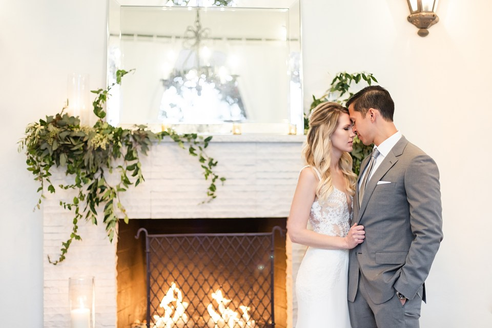 Angela & Kevan forehead to forehead in front of the fireplace during their Villa & Vine Wedding