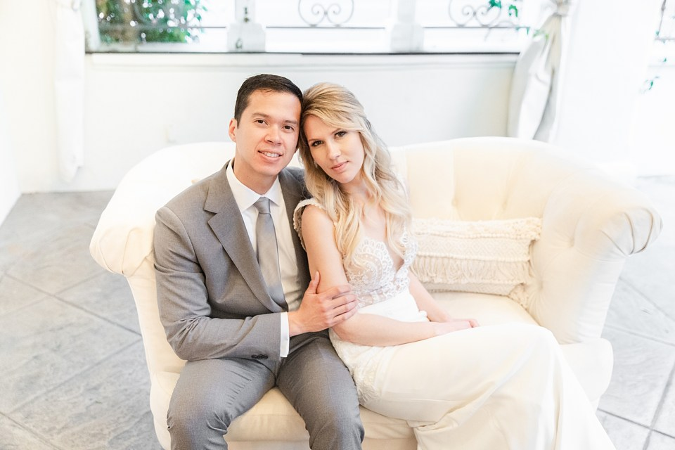 Angela & Kevan smiling at the camera while sitting on a couch during their Villa & Vine Wedding