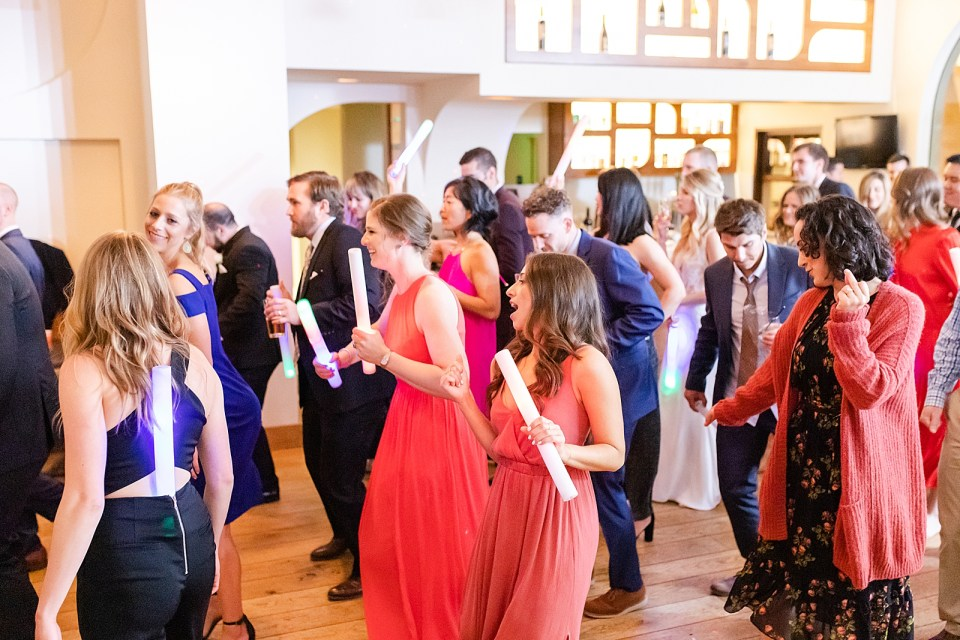 The entire wedding party participating in a dance. Smiling, laughing, and waving glow sticks around.
