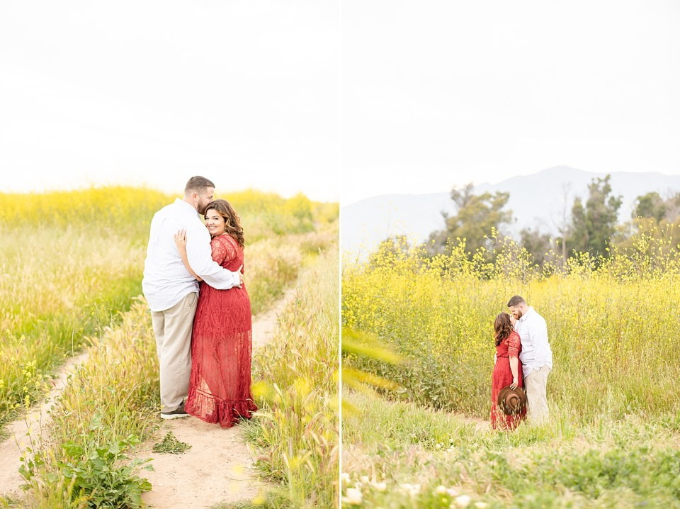 Maddy & Brian holding each other closely. Maddy is wearing a long red dress with sleeves to her elbows and Brian is wearing a white button up shirt and tan khakis. They are standing in a field of yellow flowers.