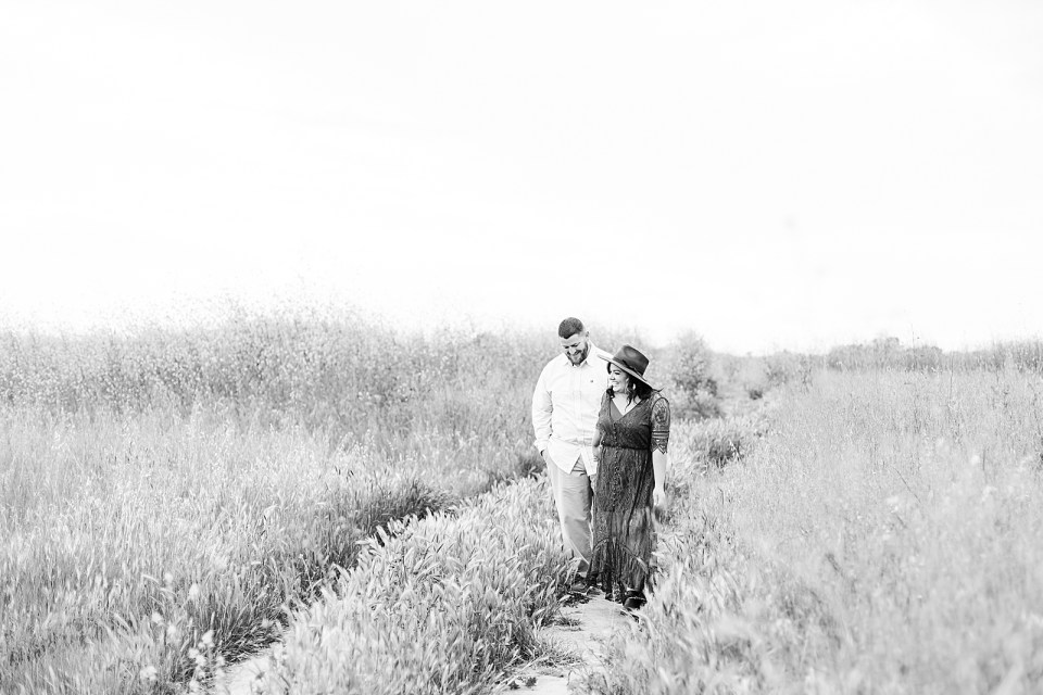A black and white image of the couple walking along a path holding hands during their Ellwood Bluffs engagement session