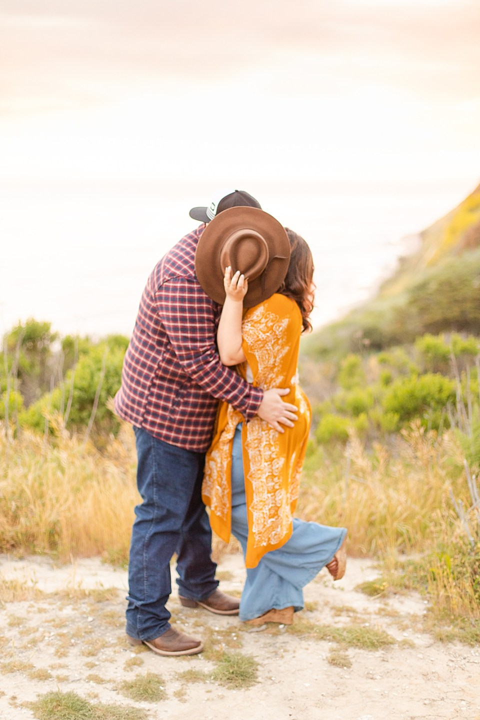 The couple kissing behind Maddy's fedora with the ocean, sunset, and many trees behind them. Maddy is popping her left foot.