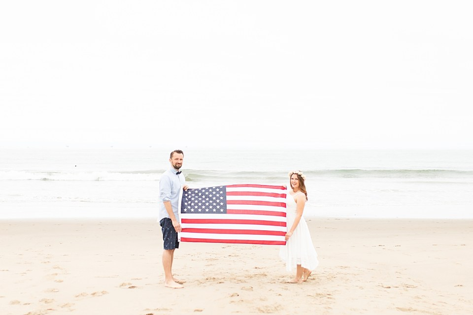 Gina & Michael holding the American flag between them with a small dolphin fin in the distance in the waves. The happy couple during their Santa Claus Beach Elopement