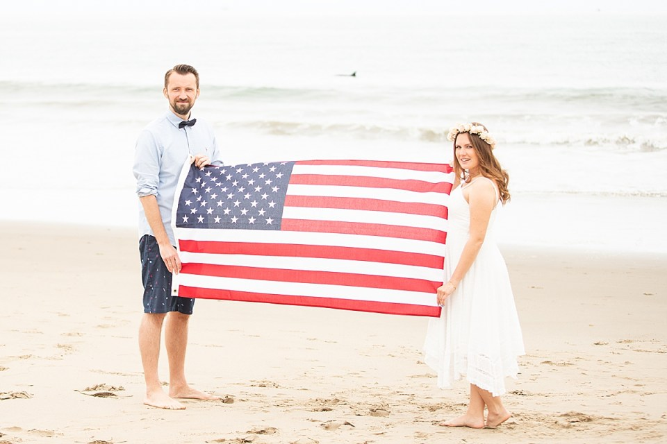 Gina & Michael holding the American flag between them with a dolphin in the waves behind them in the middle of the photo during their Santa Claus Beach Elopement