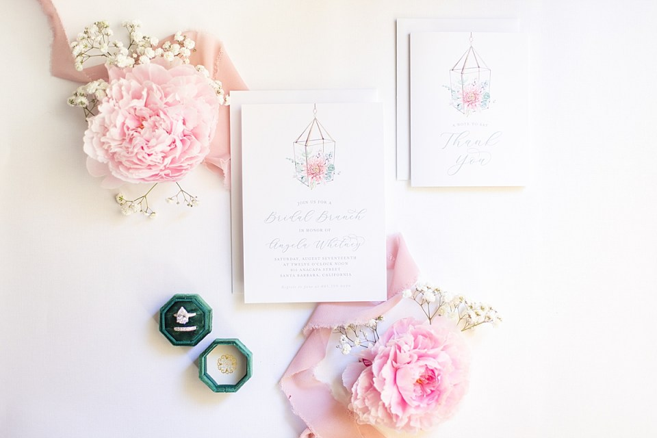 Two pink Peonies next to the couple's bridal shower brunch invitations