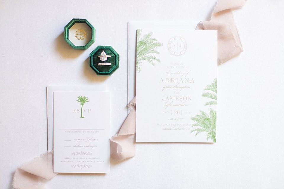 The couple's rings next to their invitations and lace.