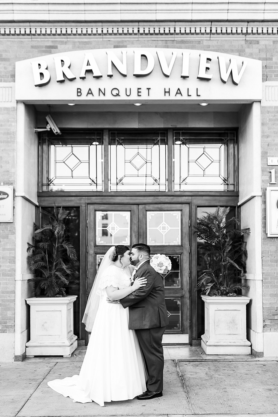 Betsy & Michael holding each other close and sharing a kiss in front of their wedding venue.