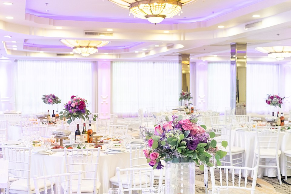 The couple's reception decor, white tables and chairs, pink and purple flowers with dark green leaves at their Brandview Ballroom Wedding.