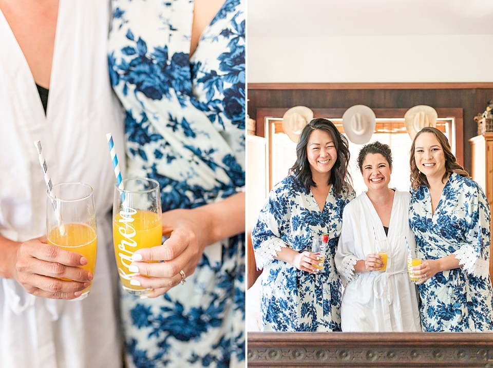 The bride with her bridesmaids wearing matching robes and holding drinks.