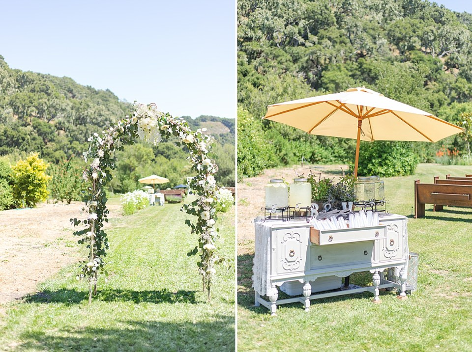The ceremony entrance covered in fresh greenery and white flowers. And a second image of a antique dresser with refreshments on top and an umbrella with pews in the background.