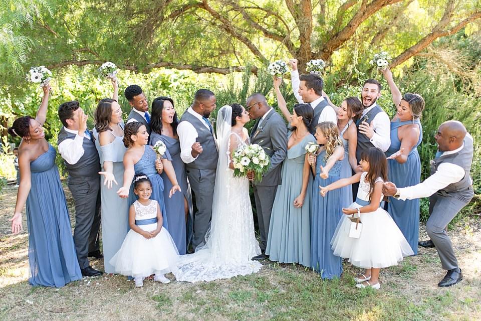 Brandi & Victor kissing as their bridal party cheers during their Rancho San Julian wedding.