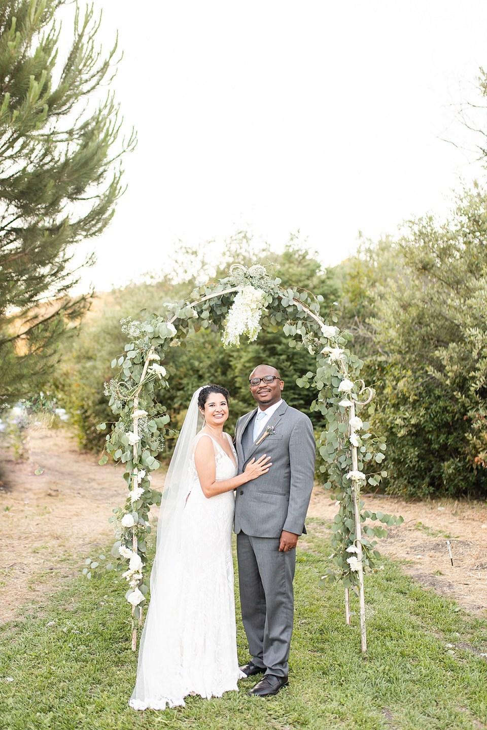 The couple smiling at the camera under their trellis.