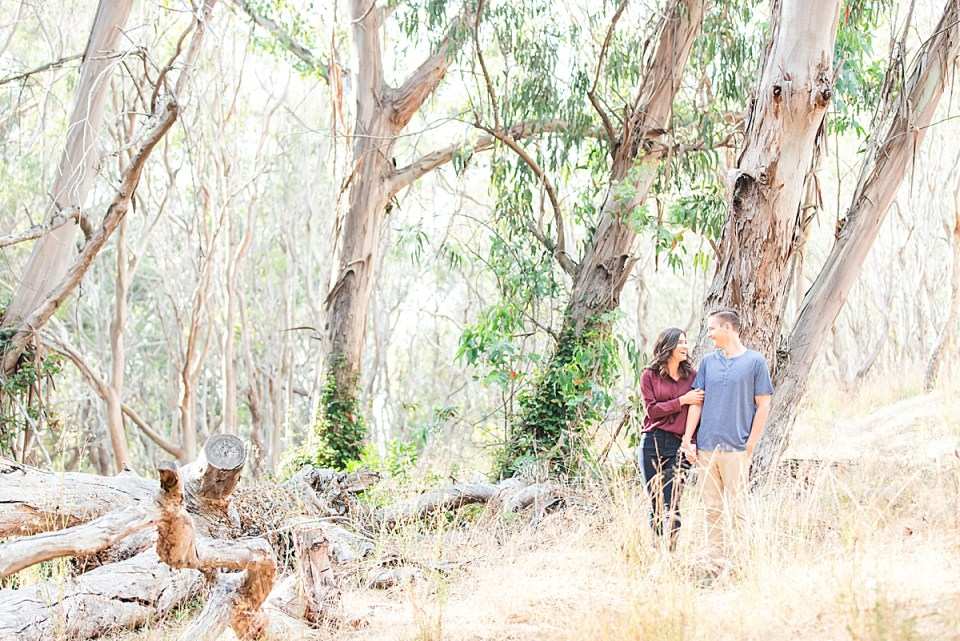 Lauren & Scott walking arm in arm through eucalyptus trees smiling at each other.