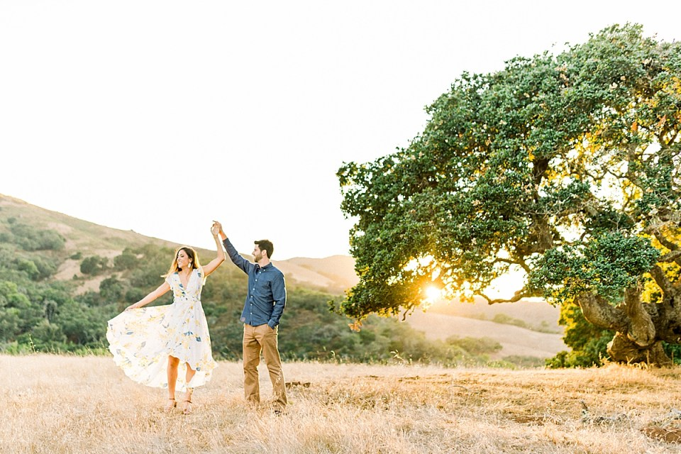 Brett is twirling Kat under the branches of an oak tree during their San Luis Obispo Bishop's Peak engagement session
