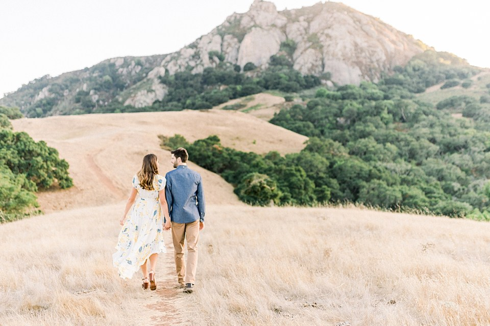 A full photo of the couple walking towards Bishop's Peak while holding hands and looking at each other. Kat's white dress is billowing in the wind.