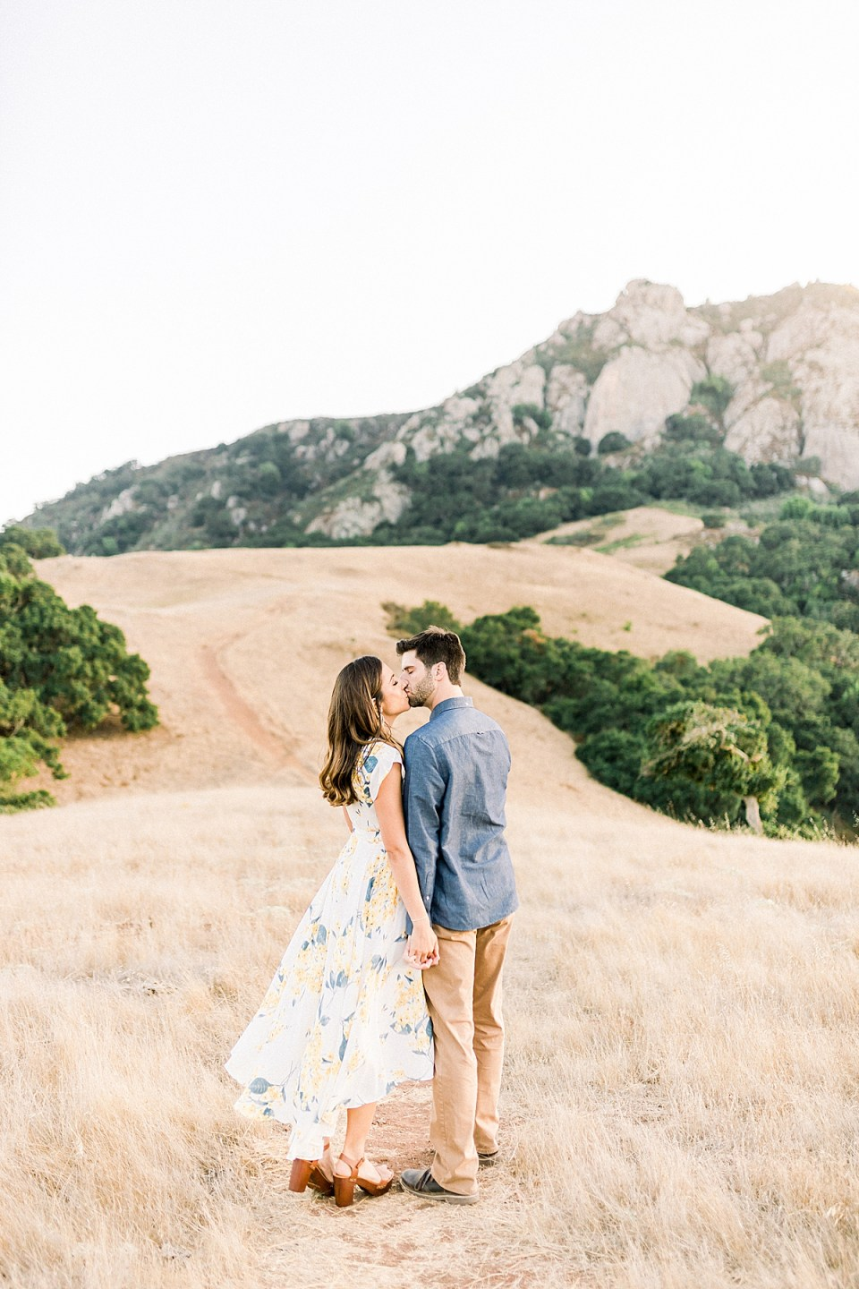 The couple stopping to share a kiss on the path while holding hands and Bishop's Peak is in the background.