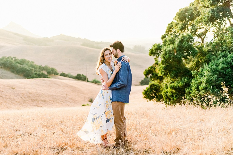 Brett smiling at Kat as Kat smiles at the camera. Her arms are around his neck and his arms are around her waist. Yellow rolling hills and green oak trees are behind them during their Bishop's Peak engagement session.