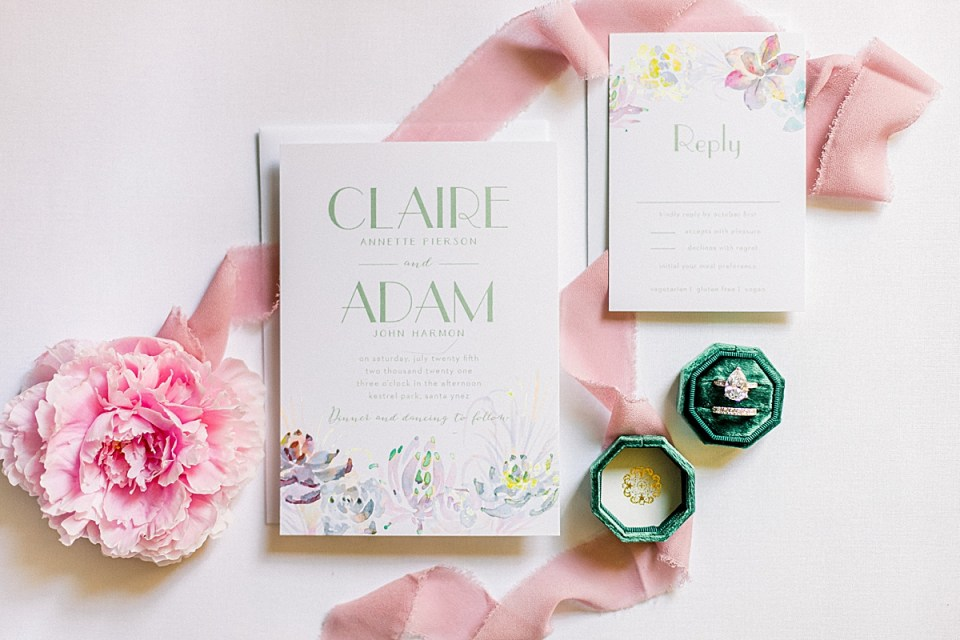 The couples Wedding Invitations with a pink peony, pink lace, and a green ring box with the bride's engagement ring and wedding band.