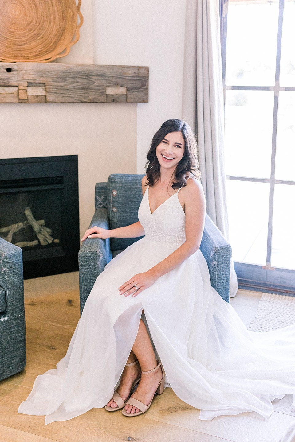 Lauren smiling at the camera while sitting in a chair after just getting dressed in her wedding gown during the couple's San Luis Obispo Farm Wedding
