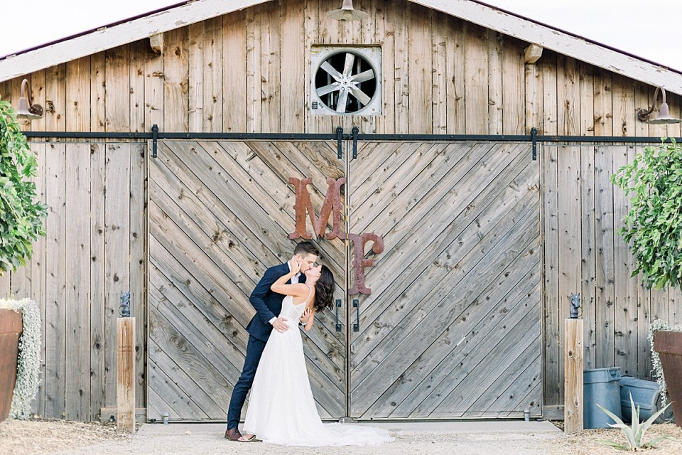 """Scott dipping his spouse and sharing a kiss with her in front of the wedding venue's barn doors that have the letters """"M"""" and """"F"""" which refers to MarFarm."""