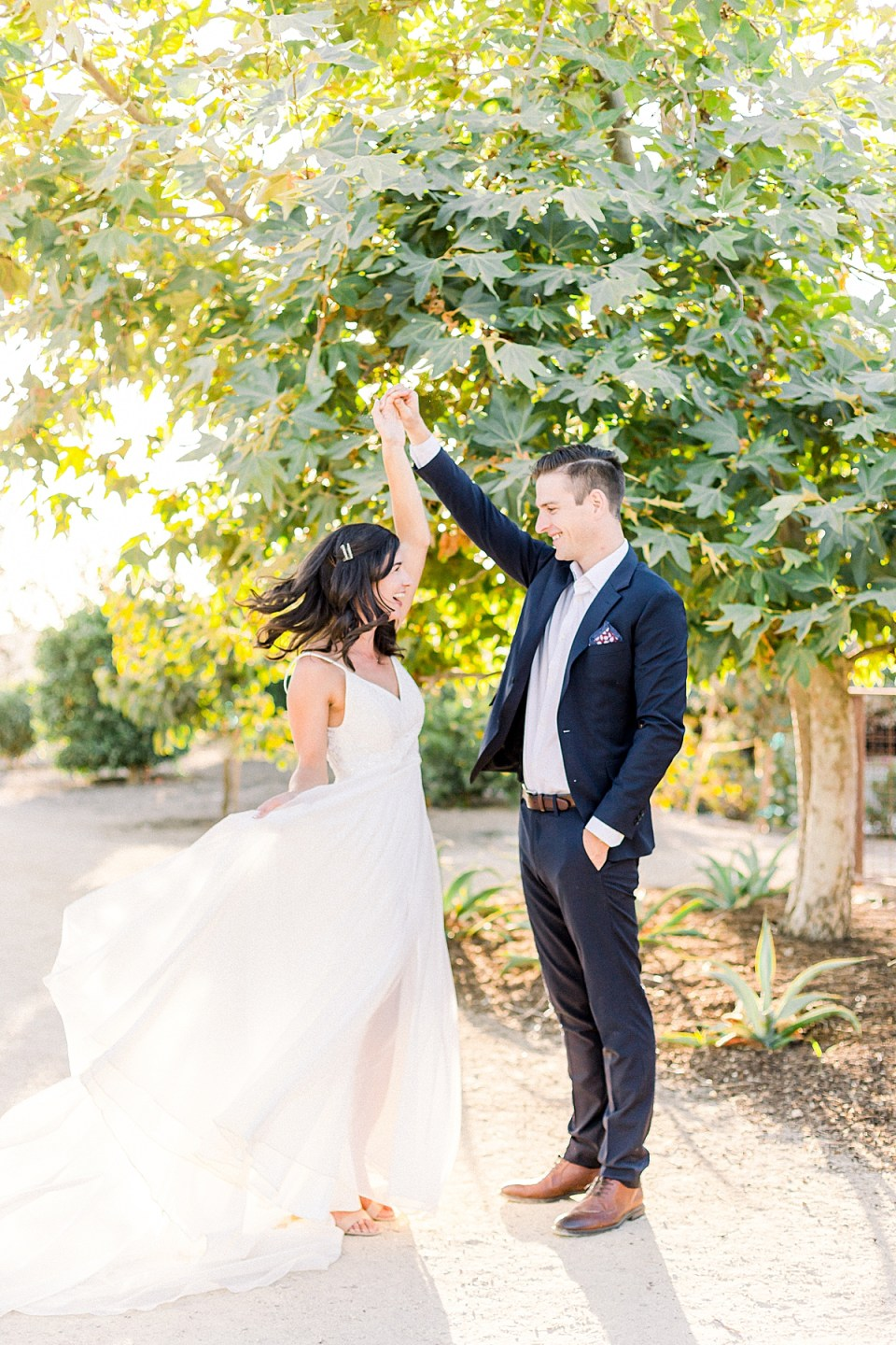 Scott twirling his wife as she smiles and laughs back at him during their San Luis Obispo Farm Wedding