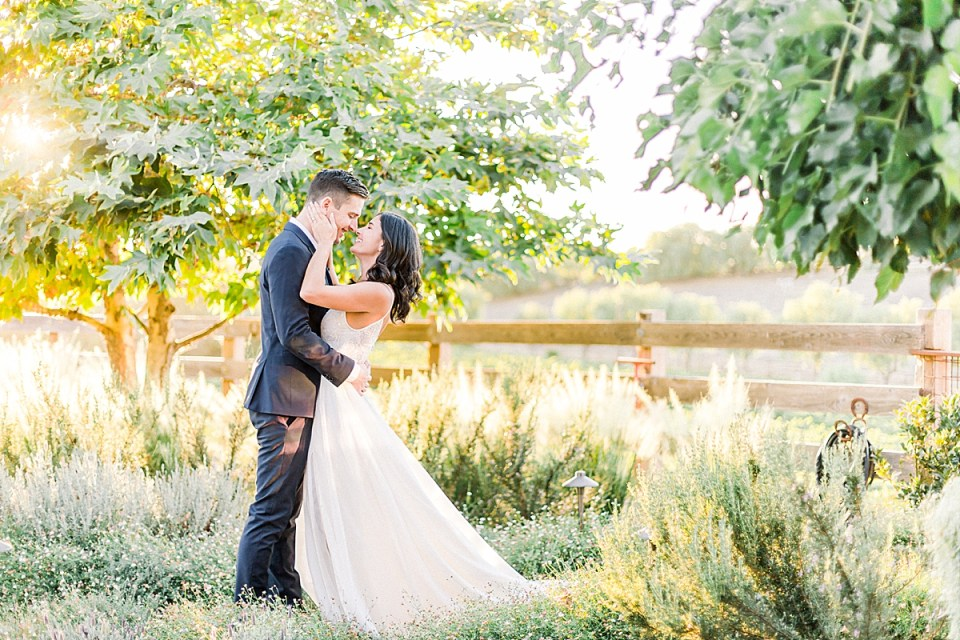 The couple sharing a moment beneath the trees and surrounded by tall grass and gardens during their San Luis Obispo Farm Wedding