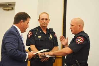 Officer Brandon Smith (right) receives his oath from Mayor Andy Moore (left) and Smithfield Police Chief Keith Powell (center) holds the Bible. Photo courtesy Town of Smithfield
