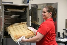 """McGee's Crossroads Elementary School Nutrition Manager Tammy Baker prepares rolls to be served during the school's """"BBQ Pitmaster"""" themed lunch as a part of National School Lunch Week on Oct. 17."""