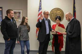 Todd Sutton (front, left) is sworn in to the Johnston County Board of Education by Senior Resident Superior Court Judge Thomas Lock (front, right). Accompany Sutton are his children Noah (back, left), Raegan (back, center), and his wife Lynda (back, right).