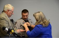 Harnett County Sheriff's Cpl. Eric Cook returned to work Monday after nearly a year of rehab from the gunshot rounds he received in the line of duty last April. As part of his return, he was awarded the Purple Heart for Law Enforcement. Here, his wife, Melissa, pins the medal on her husband.