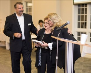 """Chamber Director Joan Pritchett and Board President Tim Barbour honor Jackie Parrish with the first """"Four Oaks Proud"""" Award."""